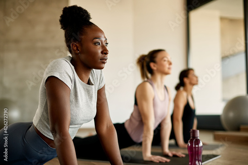 Fototapeta African American athletic woman stretching during exercise class at health club