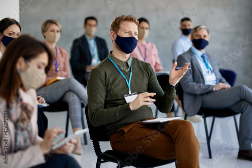 Entrepreneur with face mask talks while attending business education event in conference hall Fototapet