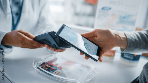 Obraz na płótnie Pharmacy Drugstore Checkout Cashier Counter: Pharmacist and a Customer Using NFC Smartphone with Contactless Payment Terminal to Buy Prescription Medicine, Health Care Goods