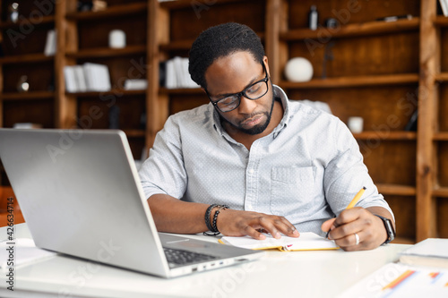 Fototapeta Focused African-American guy is using a laptop for watching webinars, taking notes, studying online