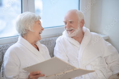 Canvas Print Senior couple in white robes choosing procedures in a spa center and looking enj