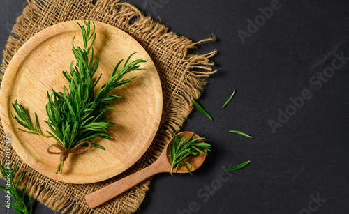 Fotografie, Obraz Top view of Branch fresh rosemary in wood plate on black  background