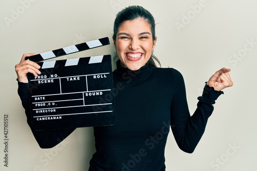 Fotomural Young hispanic woman holding video film clapboard screaming proud, celebrating v