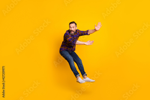 Full length body size photo of man jumping flying back while windy storm isolated on vibrant yellow color background