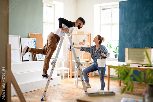 Mid adults couple having fun when painting indoors at home, relocation and diy concept.