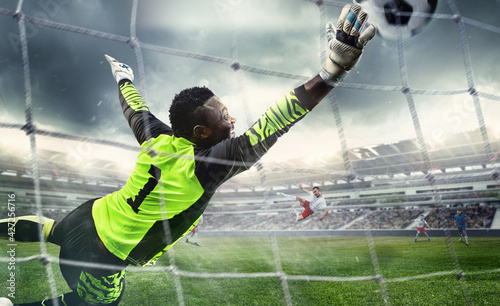 Foto African male soccer or football player, goalkeeper in action at stadium
