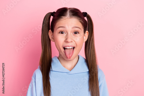 Photo portrait of funky schoolgirl showing tongue fooling playful isolated on pa Fototapeta