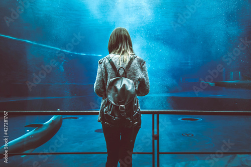 Young girl in aquarium tunnel with dolphins - Woman visitor at aqua park looking at animals - People and animals concept