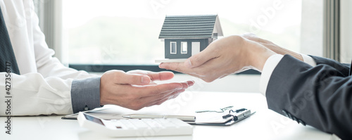 Valokuva The real estate agent gives the house to a new owner's client after completing the signing of the lease and formally completing home insurance