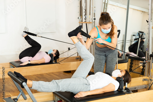 Fototapeta Female pilates trainer in protective mask helping a pilates woman during trainin