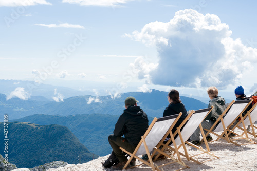 Canvastavla Group of people sitting in the deck chairs on a mountain top watching clouds abo