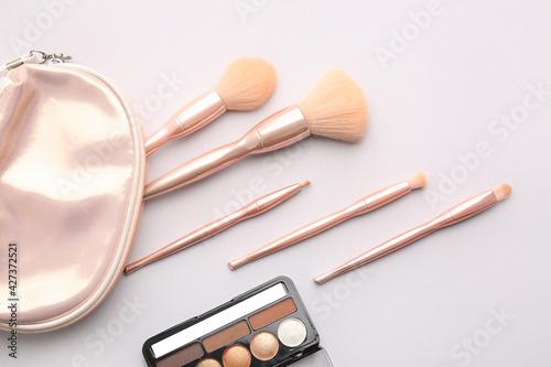 Valokuva Bag with stylish makeup brushes and eyeshadows palette on light background