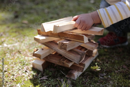 Photo boy working on a stack of firewood kindling at a garden