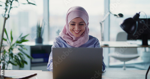 Canvas Print Young happy arabic woman receiving successful job invitation business email clenching fist rejoicing inside corporate office