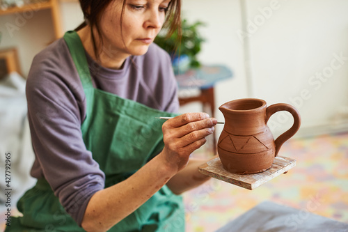 Canvas woman potter applies a pattern with a tool on the surface of an earthen jug