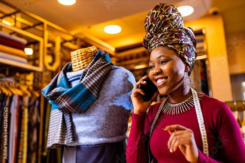 Fototapeta tanzanian woman with snake print turban over hear working in fabrics shop callin