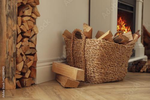 Fototapeta Basket with firewood on floor in room