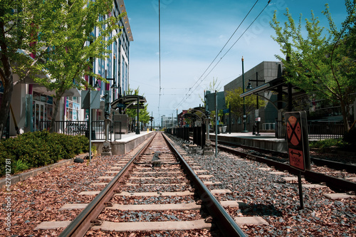 Fotografie, Obraz Low angle view of light rail tracks leading to platform in Charlotte, North Caro