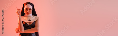 Canvas Print young nun in sexy dress holding cigarette isolated on pink, banner