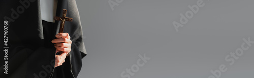 Fotografering partial view of nun in black vestment holding cross isolated on grey, banner