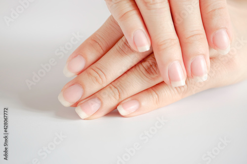 Photo Closeup of beautiful hands and fingernails of woman on white background, Concept of health care of the fingernail