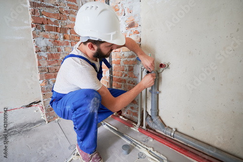 Canvas Man in safety helmet lubricating water pipe to reduce friction and provide long-lasting lubrication