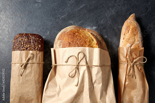 Fototapeta food, baking and cooking concept - close up of bread in paper bags on table over