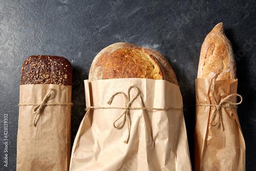 Billede på lærred food, baking and cooking concept - close up of bread in paper bags on table over