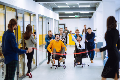 Fotomural Friendly work team  ride chairs in office room cheerfully excited diverse employees laugh while enjoying fun work break activities, creative friendly workers play a game together