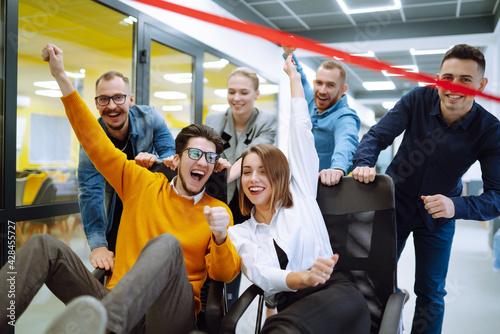 Fotografering Friendly work team  ride chairs in office room cheerfully excited diverse employees laugh while enjoying fun work break activities, creative friendly workers play a game together