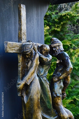 Bronze religious sculptural group from Calvary, fifth Station Of The Cross - Simon of Cyrene helps Jesus carry the Cross Fototapeta