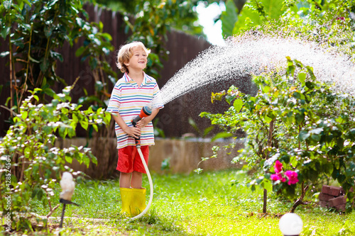 Fotografia Boy watering flower in garden. Kid with water hose