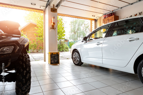 Valokuva Home suburban countryside modern car and ATV double garage interior with wooden shelf, tools and equipment stuff storage warehouse indoors against sun light