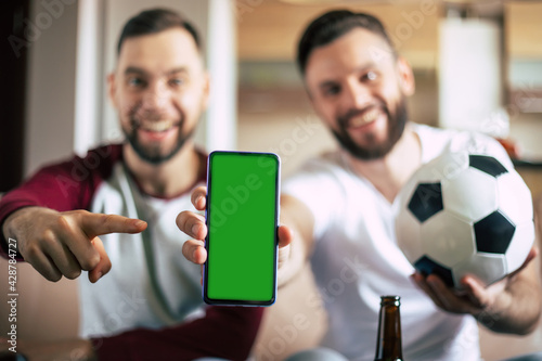 Canvas Close up mockup photo of green blank screen on the smart phone in hand of excited young bearded sports fans