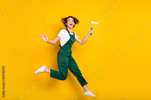 Full size photo of happy smiling good mood funky girl painter jumping wear uniform overall isolated on yellow color background