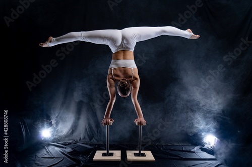 Fotografiet Flexible circus artist - female acrobat doing handstand on the back and smoker b