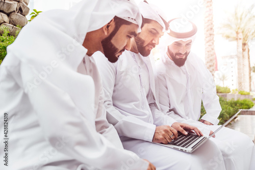 Photo Three arabic men talking about business outddor