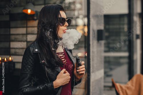 Obraz na płótnie Beautiful stylish brunette smoking an e-cigarette in public places