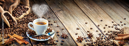 Foto Coffee Espresso Cup With Beans And Cinnamon On Wooden Table