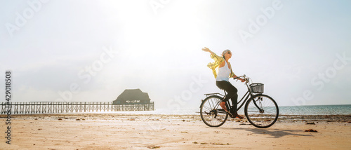 Canvas Print Young female dressed light summer clothes joyfully threw up her hand riding old vintage bicycle with front basket on the low tide ocean white sand coast on Kiwengwa beach on Zanzibar island, Tanzania