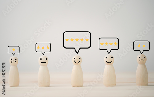 Fotografiet Wooden doll with emotion face and yellow stars for customer evaluation and satisfaction for product and service