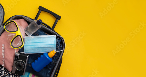 Obraz na plátně Suitcase packed for a summer vacation during the coronavirus global pandemic