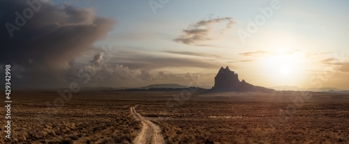Foto Striking panoramic landscape view of a dirt road in the dry desert with a mountain peak in the background