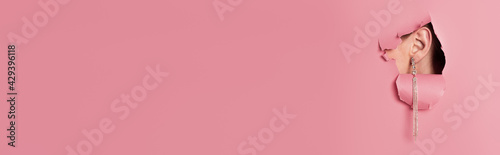 Fotografiet Cropped view of woman with stylish earring near pink background with hole, banne