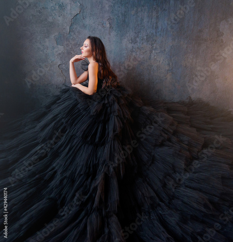 Fotografiet Side view of brunette in a lush black dress sitting on a background of the wall