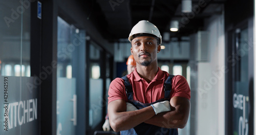 Canvas-taulu Portrait of professional young engineer architec afro-american worker in protective uniform smiling posing for camera in construction new building