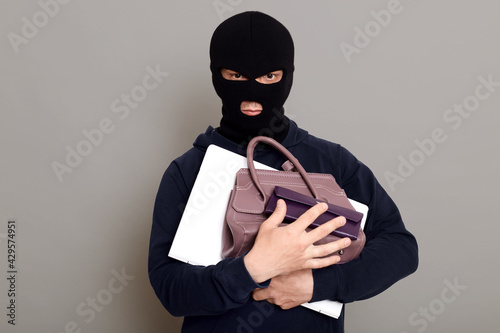 Canvastavla Serious male thief holding bunch of stolen things, laptop, wallet and woman's handbag, robber wearing mask and black turtleneck, burglar isolated over gray background
