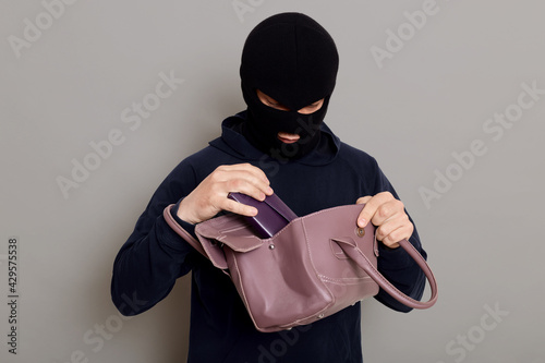 Fotografia Young male burglar steals woman's handbag, opens bag and looking inside, pulls out wallet, wearing black sweater and burglar mask, robber posing isolated over gray background