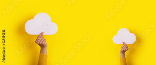 Two hands holding paper cloud over yellow background, panoramic image, cloud storage concept