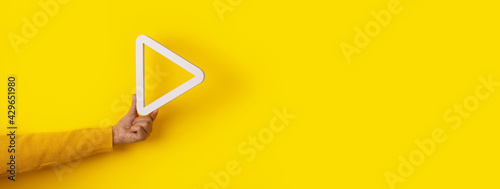 Fotografie, Obraz 3d media play button in hand over yellow background, panoramic layout